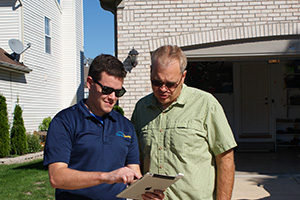Technician reviews gutter cleaning with homeowner
